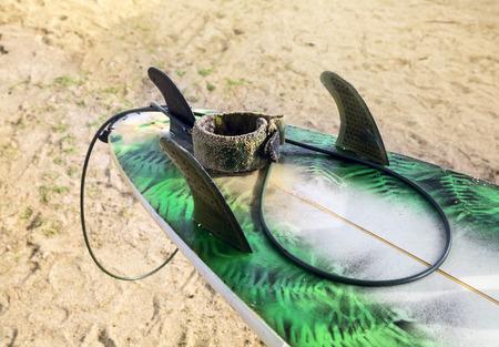 surfboard fin: Fish Surfboard lying on sand on the beach near the ocean Stock Photo