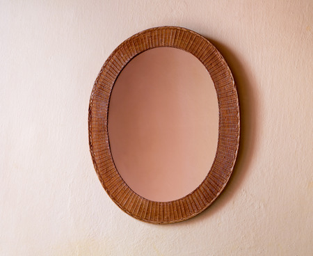 penumbra: Mirror in a wicker frame hanging on the wall beige color