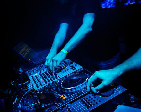Dj mixes the track in the nightclub at party photo