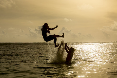 expiring: Silhouette of young girl jumping out of the ocean, which throws strong two man on the background of the expiring sunset. Single shooting Stock Photo