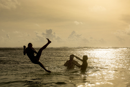 expiring: Silhouette of young girl jumping out of the ocean, which throws strong two man on the background of the expiring sunset  Single shooting Stock Photo