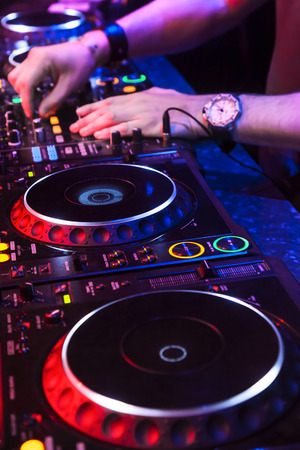 dj mixer: Dj mixes the track in the nightclub at party