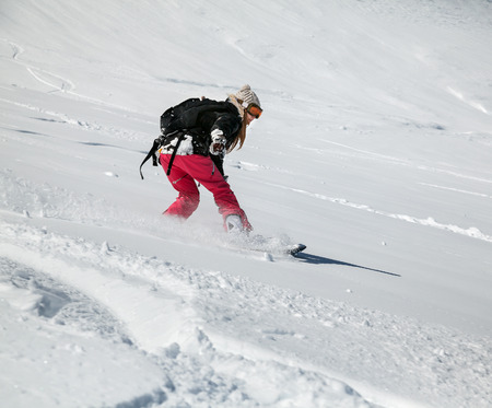 Young girl snowboarder in motion on snowboard in mountains photo