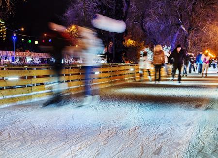 patinaje sobre hielo: Las personas son el patinaje en el parque en una pista de patinaje en invierno