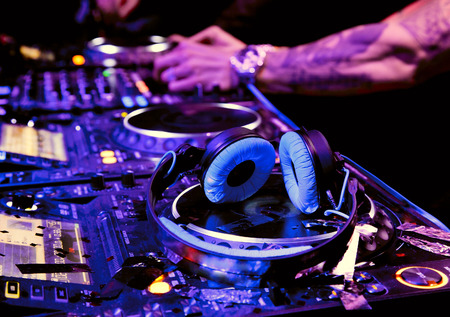 Dj mixes the track in nightclub at party. DJ headphones Stock Photo
