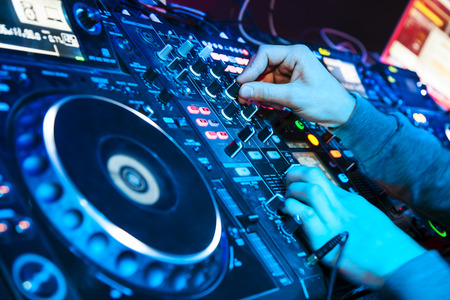 discotheque: Dj mixes the track in the nightclub at party