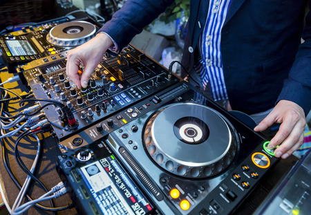 disc jockey: Dj mixes the track in the nightclub at party