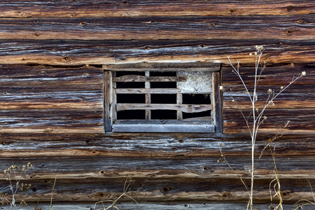 without window: Fragment old wooden log house with a window without glass in russian village