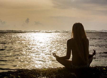 Silhouette of beautiful woman with dreadlocks on his head, sitting near the ocean, meditating at sunset photo