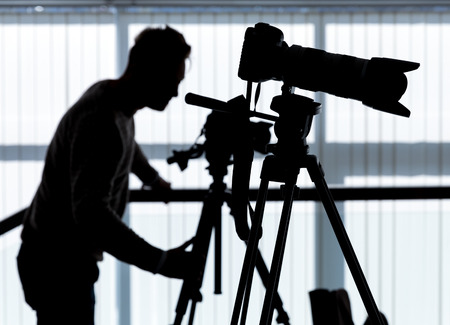 Silhouette of photographer and cameraman shot the video on a tripod at the workplace indoors photo