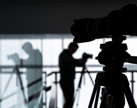 Silhouette of photographer and cameraman shot the video on a tripod at the workplace indoors Standard-Bild