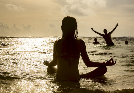mind body: Silhouette of beautiful woman with dreadlocks on his head, sitting near the ocean, meditating at sunset Stock Photo