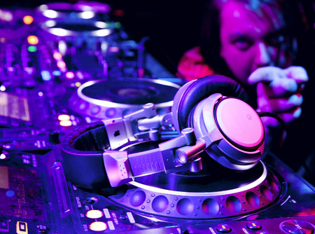 Dj playing the track in nightclub at party. DJ headphones photo