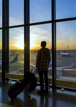 Silhouette of man with luggage standing near window in airport photo