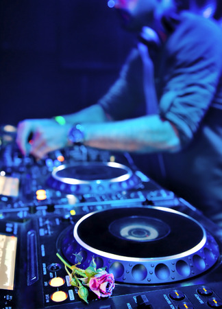 Dj mixes the track in the nightclub at party. Rose in the foreground photo