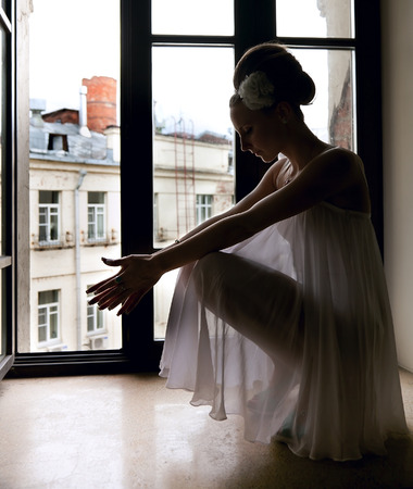 Silhouette of a beautiful thoughtful bride sitting on window sill photo