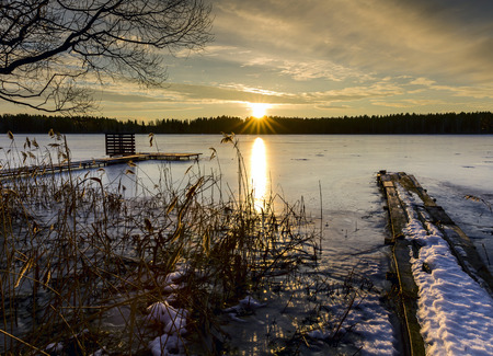 Sunset on a cold winter evening in the Russian province on the background of a frozen lake and pier photo