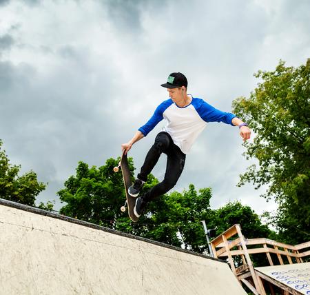 スケート ボードのハーフパイプのスケートパークに背景の空曇りジャンプ