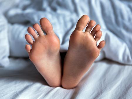 Baby feet on bed under white blanket photo