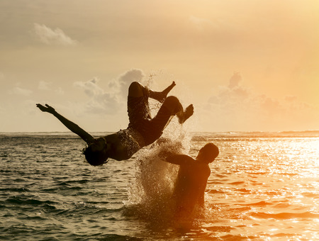 expiring: Silhouette of young man jumping out of the ocean, which throws strong two man on the background of the expiring sunset