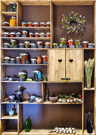 store shelf: Domestic stocks with pickled vegetables in glass jars on wooden shelves Editorial