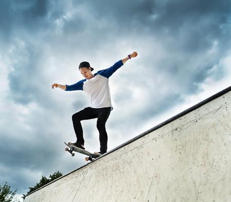 halfpipe: Skateboarder jumping in halfpipe at skatepark  Stock Photo