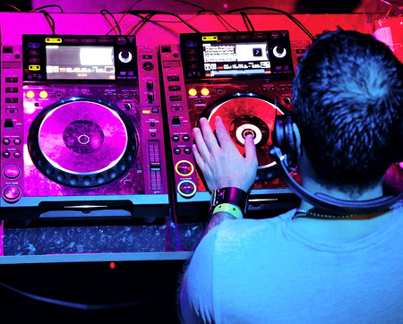 Dj in headphones mixes the track in the nightclub at party photo