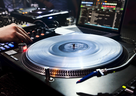 dj turntable: Dj mixes the track in the nightclub at party  Vinyl Player in foreground Stock Photo