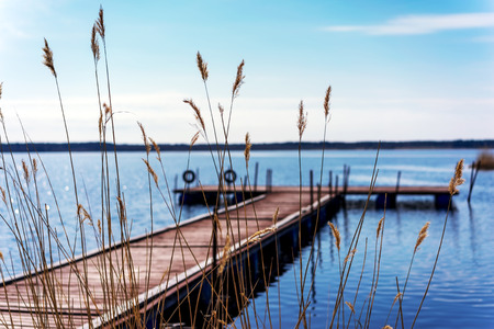 Pier for pleasure and fishing boats on shore of Lake Ladoga in Karelia. Soft focus. In the foreground the tall grass
