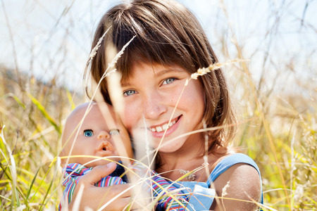combed: Portrait of attractive beautiful young girl with childrens doll in his hand, among the tall grass