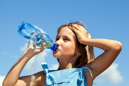 8 10 years: Attractive young beautiful girl drinking water from plastic bottles