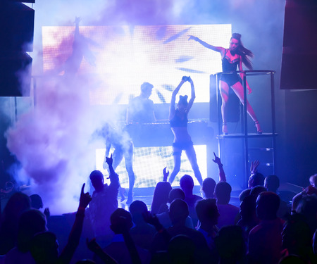 audio mixer: Dj playing on stage in smoke. Silhouettes female dancers and people in motion, dancing at nightclub