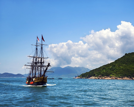 Historic old ship in the ocean near the islands and beautiful\ panorama