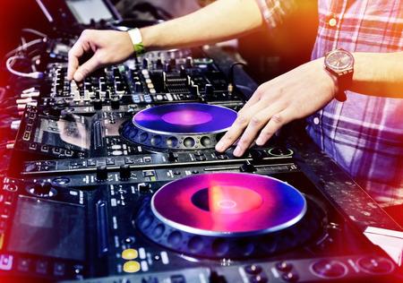 fiestas electronicas: DJ mezcla la pista en el club nocturno en el partido