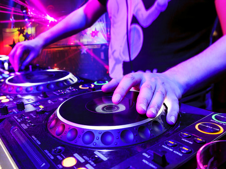 Dj mixes the track in the nightclub at party. In the background laser light show photo