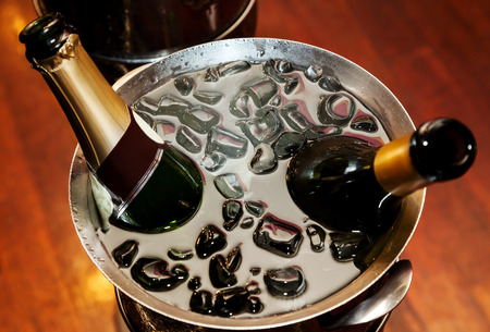 Two bottles of chilled champagne on ice in metal container photo