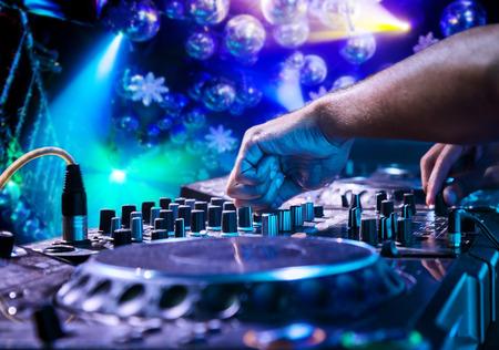 fiesta dj: DJ mezcla la pista en el club nocturno en la fiesta. En el fondo espect�culo de luz l�ser