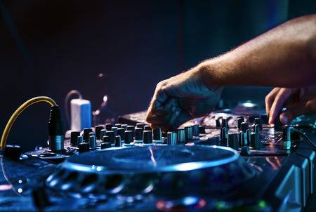 audio mixer: Dj mixes the track in the nightclub at party