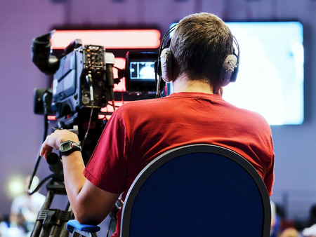 film: Professional cameraman with headphones with HD camcorder in live television