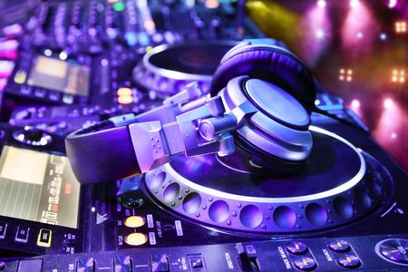 ナイトクラブで、ヘッドフォンを dj ミキサーです。 背景のレーザー光のショーで