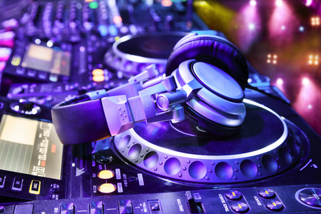 Dj mixer with headphones at nightclub.  In the background laser light show Stok Fotoğraf