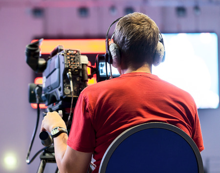 tv camera: Professional cameraman with headphones with HD camcorder in live television