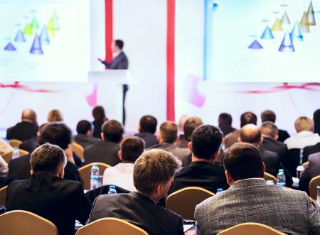 Spreker op het podium, Mensen aan de conferentiezaal in Achteraanzicht Stockfoto