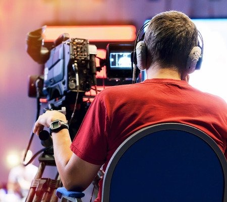 Professional cameraman with headphones with HD camcorder in live television photo