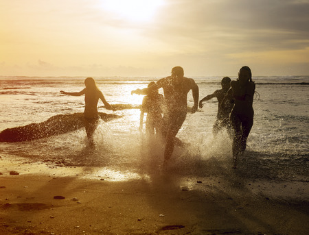 Silhouettes of group friends running out of the ocean on the beach during sunset