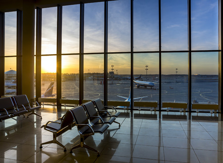 airport lounge: Silhouettes of bench in interior in airport lounge on background of the airfield with passenger planes