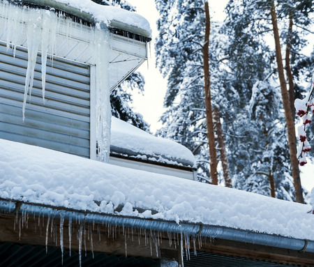 Corner of country house with icicles on roof in winter. Pine trees in background photo