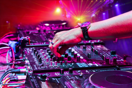 audio mixer: Dj mixes the track in the nightclub at party  In the background laser light show Stock Photo