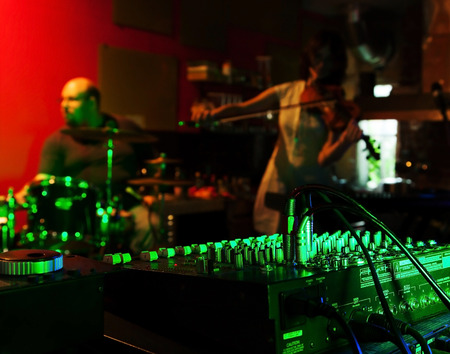 record studio: Music Mixer at nightclub with connected wires. In the background, the musicians play live music