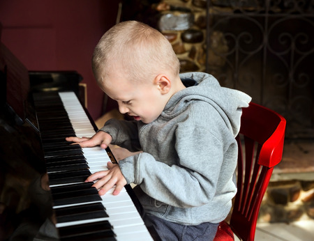 Emotional little boy learning to diligently play on the piano